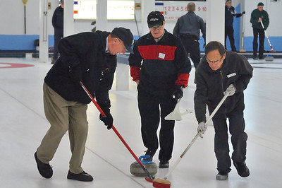 Barrie Brown (L) and Bob Takashiba (R) sweeping the rock while Monty Scarrow (C) looks on