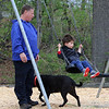 Richard Karlen of Natick, with his rescue dog, Jersey, watches his grandson Weston Martel, 2-1/2, of Chelmsford, on the swings at Varney Playground in North Chelmsford. JULIA MALAKIE/LOWELLSUN