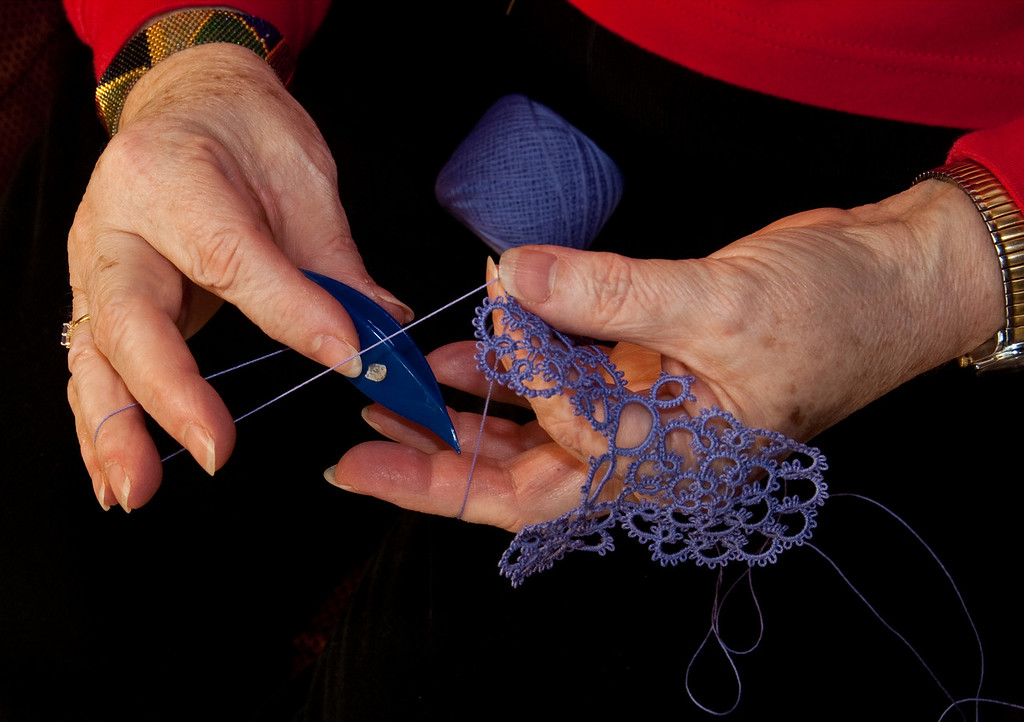 Tatting reminds me of Native American finger weaving, in the way that Wahneta winds the thread around her fingers in a very precise pattern. <br /> <br /> The thread is then fed through the loops on a shuttle (the blue tool in her right hand in this picture).