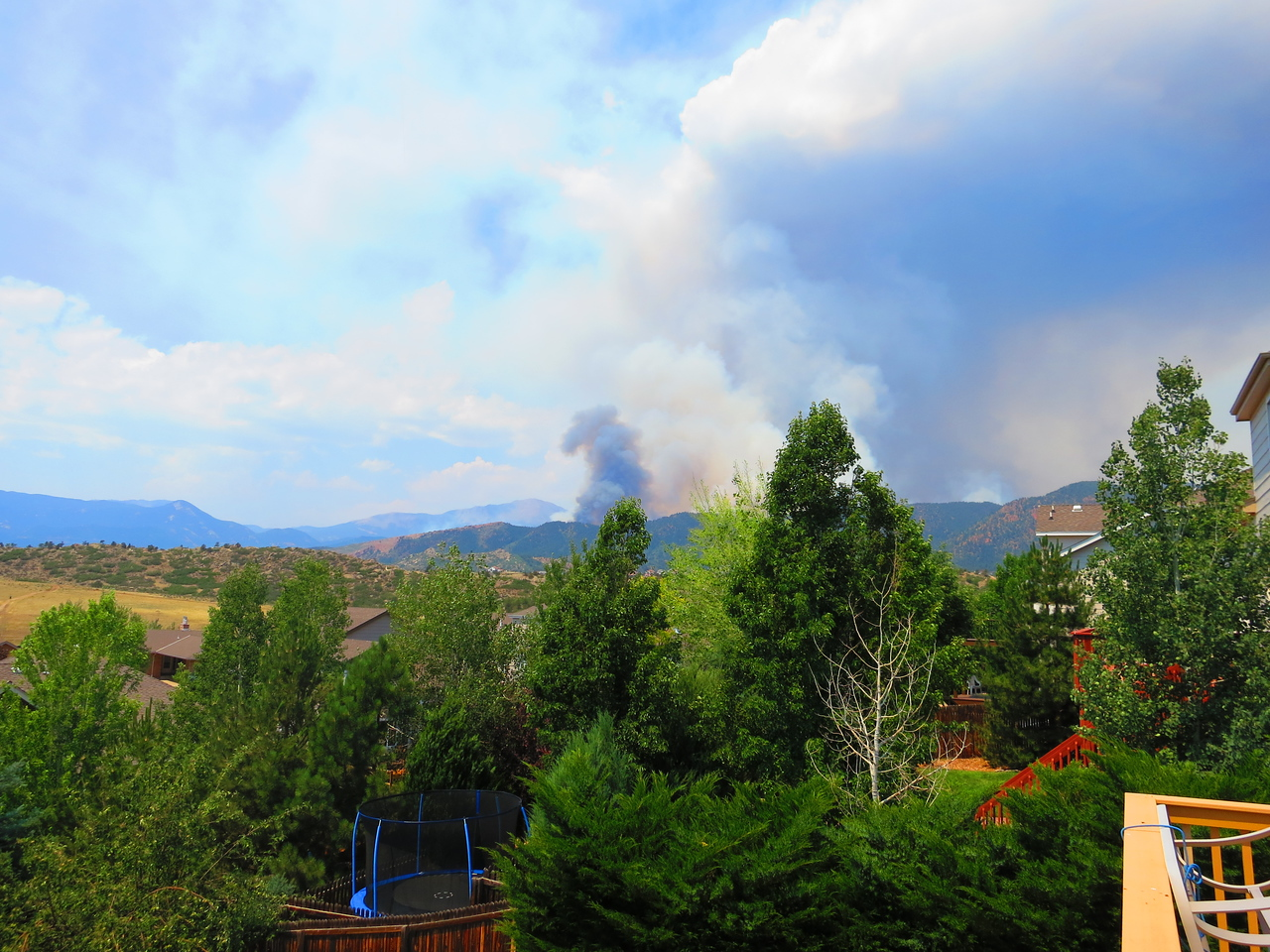 View SW from my back deck: Sunday, June 24th - 11:30 am. Pikes Peak summit just left of dark smoke.