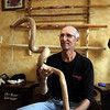 James Sarantakis of Lowell, in his apartment, with a walking stick made from a section of bittersweet vine that grows around trees. It's one of the walking sticks he's made from wood gathered along the river. (SUN/Julia Malakie)
