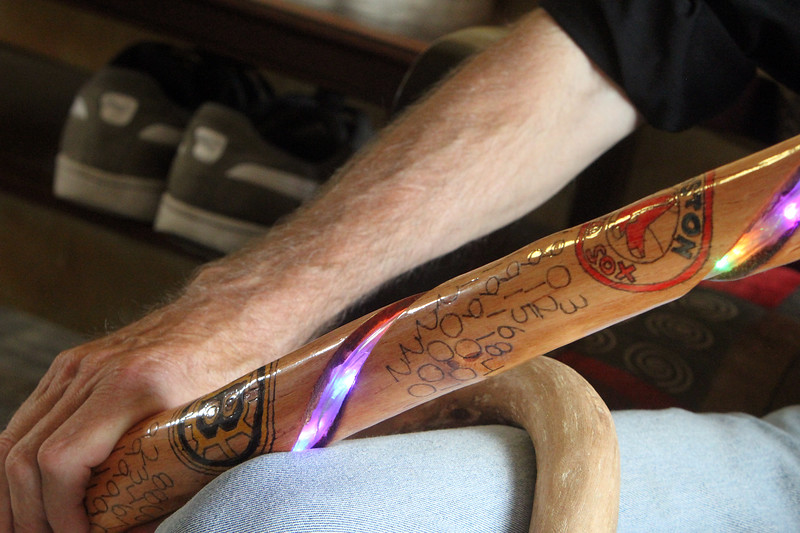 James Sarantakis of Lowell, in his apartment, with his sports stick, notiing the championships of the four major Boston sports teams. It's one of the walking sticks he's made from wood gathered along the river. (SUN/Julia Malakie)