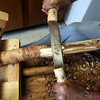 James Sarantakis of Lowell, in his apartment kitchen, uses a draw blade to remove bark from a piece of river birch He makes walking sticks from wood gathered along the river. (SUN/Julia Malakie)