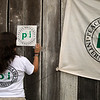 Elena puts up the PBI flag and sign in the place where the women's event will take place.