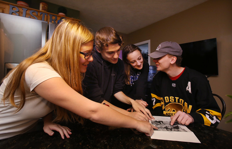 Cornetta quadruplets from Westford are 18, and graduating from high school. From left, Jessica, Dan, Kimberly and Joe look at newspaper clipping about them at age one.  (SUN/Julia Malakie)