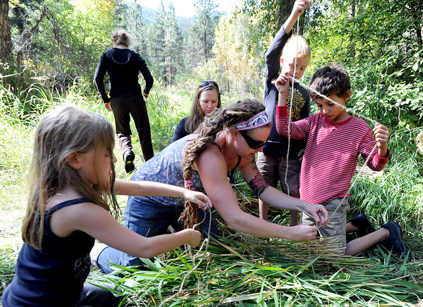"Sage Bookman, left, Nicole Bookman, back, Natalie Eamonn, Cedar Eamonn and Emmette Manzella, put together a door for the grass hut during class.<br /> Simon Harrison teaches a ""primitive skills"" class at Lion's Gulch, outside Pinewood Springs.<br /> For a video and more photos of the program, go to  <a href=""http://www.dailycamera.com"">http://www.dailycamera.com</a>.<br /> Cliff Grassmick / September 16, 2011"