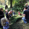 "Nicole Bookman, left, talks to her children, while Simon Harrison, right, picks up the grass door to put on  hut.<br /> Simon Harrison teaches a ""primitive skills"" class at Lion's Gulch, outside Pinewood Springs.<br /> For a video and more photos of the program, go to  <a href=""http://www.dailycamera.com"">http://www.dailycamera.com</a>.<br /> Cliff Grassmick / September 16, 2011"