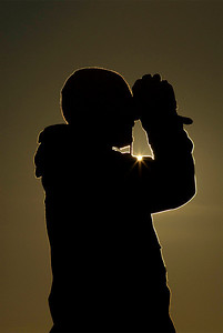 Silhouette of person viewing wildlife with binoculars