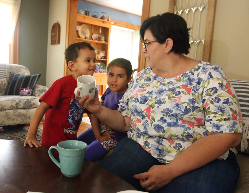 . Michelle Chioccola, who grew up in Wilmington and now lives in Abu Dhabi, where she works at a school for autistic children, visits her family in Wilmington. Michelle Chioccola consults her son Ziyad Achraf, 4, and daughter Noura Achraf, 5, about which UAE prince is pictured on a mug. (SUN/Julia Malakie)