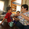 Michelle Chioccola, who grew up in Wilmington and now lives in Abu Dhabi, where she works at a school for autistic children, visits her family in Wilmington. Michelle Chioccola consults her son Ziyad Achraf, 4, and daughter Noura Achraf, 5, about which UAE prince is pictured on a mug. At left is her mother Linda Chioccola. (SUN/Julia Malakie)