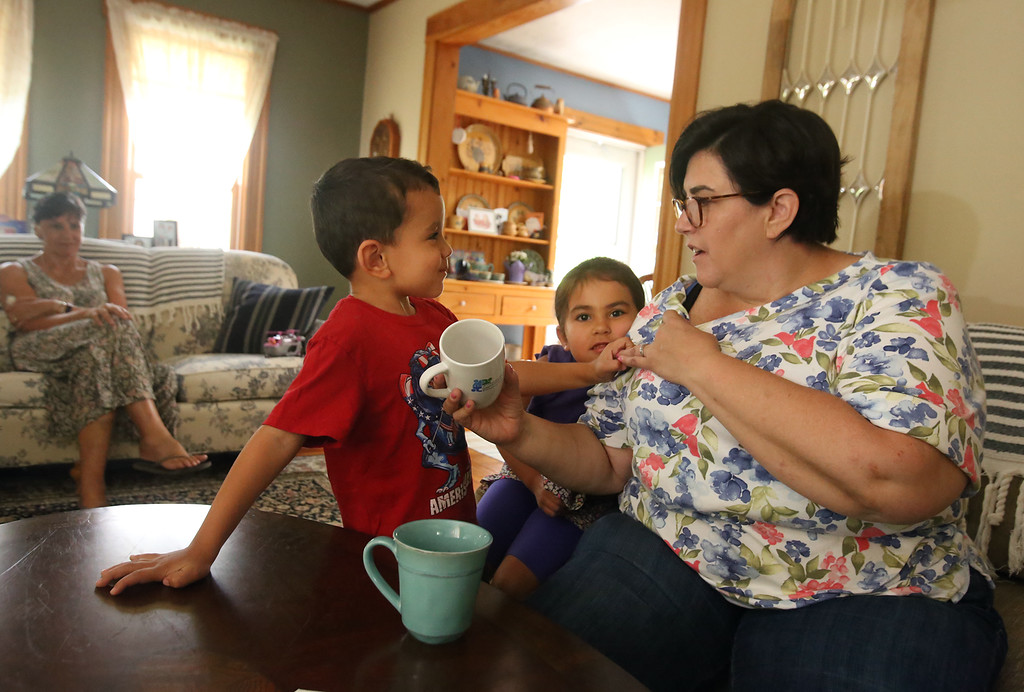 . Michelle Chioccola, who grew up in Wilmington and now lives in Abu Dhabi, where she works at a school for autistic children, visits her family in Wilmington. Michelle Chioccola consults her son Ziyad Achraf, 4, and daughter Noura Achraf, 5, about which UAE prince is pictured on a mug. At left is her mother Linda Chioccola. (SUN/Julia Malakie)