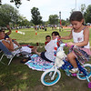 Wilmington 4th of July - 25th Annual WIlmington Family Day, at Town Common. Noura Achraf, 5, of Abu Dhabi, sits on a bike borrowed from her cousin for the decorated bike parade event. Her mother Michelle Chioccola, right rear, holding son Ziyad Achraf, 4, grew up in Wilmington and they are visiting family for most of July. It's Noura's first 4th of July in Wilmington, because they usually visit at Christmas. (SUN/Julia Malakie)