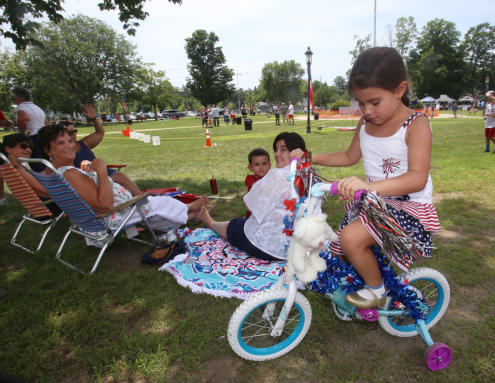 . Wilmington 4th of July - 25th Annual WIlmington Family Day, at Town Common. Noura Achraf, 5, of Abu Dhabi, sits on a bike borrowed from her cousin for the decorated bike parade event. Her mother Michelle Chioccola, right rear, holding son Ziyad Achraf, 4, grew up in Wilmington and they are visiting family for most of July. It\'s Noura\'s first 4th of July in Wilmington, because they usually visit at Christmas. (SUN/Julia Malakie)