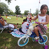 Wilmington 4th of July - 25th Annual WIlmington Family Day, at Town Common. Noura Achraf, 5, of Abu Dhabi, sits on a bike borrowed from her cousin for the decorated bike parade event. Her mother Michelle Chioccola, grew up in Wilmington and they are visiting family for most of July. It's Noura's first 4th of July in Wilmington, because they usually visit at Christmas. (SUN/Julia Malakie)