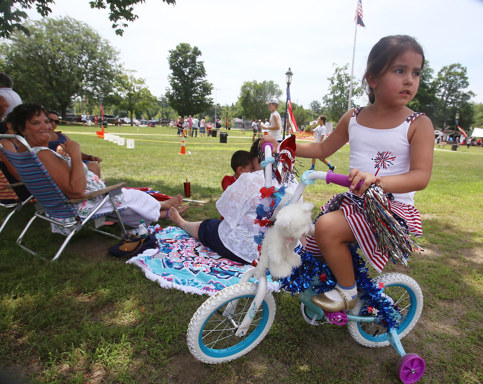 . Wilmington 4th of July - 25th Annual WIlmington Family Day, at Town Common. Noura Achraf, 5, of Abu Dhabi, sits on a bike borrowed from her cousin for the decorated bike parade event. Her mother Michelle Chioccola, grew up in Wilmington and they are visiting family for most of July. It\'s Noura\'s first 4th of July in Wilmington, because they usually visit at Christmas. (SUN/Julia Malakie)