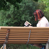 """Sabrina Hewitt of Wilmington reads """"State of Fear,"""" a novel about global warming by Michael Crichton, at the park by Silver Lake on Rt 38 in Wilmington. (SUN/Julia Malakie)"""