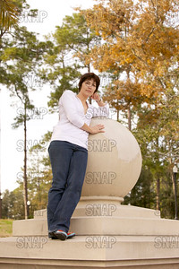 A beautiful young woman leans against a sphere in the fall.