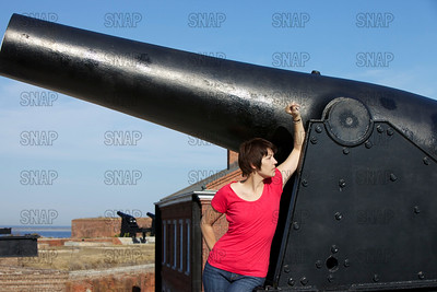 A beautiful young model poses next to a Civil War Rodman Columbiad cannon with other cannons, buildings and a river in the background.
