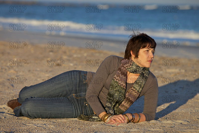 A beautiful young model poses on a cool December day on a beach along the Atlantic Ocean in Florida.
