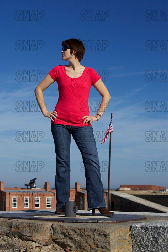 A beautiful young model poses at a Civil War fort standing on a Rodman Columbiad cannon emplacement with one of the cannons in the background.