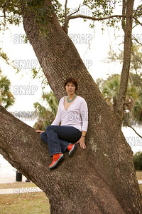 A beautiful young woman posing in a live oak tree with a river in the background.