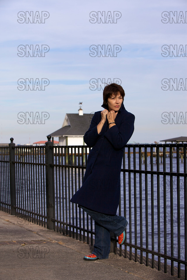 A beautiful young woman poses in the winter along a north Florida shore with a boat house in the background.