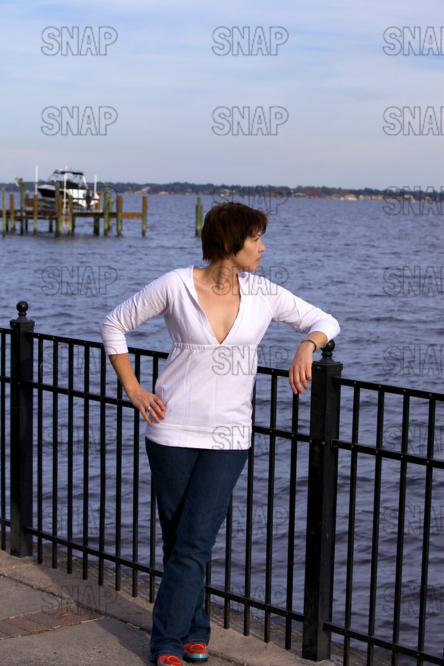 A beautiful young woman posing along a river with a boathouse in the background.