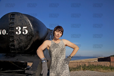A beautiful young model poses next to a Civil War Rodman Columbiad cannon with the shoreline in the background.