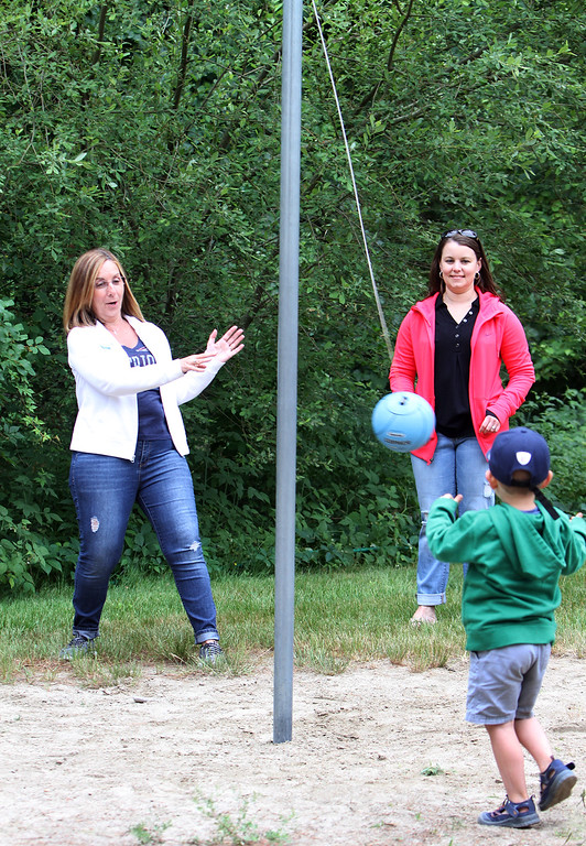 . Large family reunion of members of the Young family, at Camp Massapoag. Darlene Slates of Tyngsboro, left, her nephew\'s wife Katie Frechette of Raymond, N.H., and Katie\'s son Jackson Frechette, 4, play tetherball. (SUN/Julia Malakie)