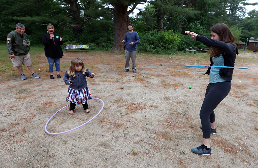 . Large family reunion of members of the Young family, at Camp Massapoag. Sophia Bagrowski, 3, and her sister Jessica Duchesne, 23, of Dracut, do hula hoops. Watching are their parents Stanley Bagrowski and Laurie Duchesne, and Jessica\'s boyfriend Jeff Breen of Dracut. Laurie is a daughter of Robert Young, 84, of Dracut. (SUN/Julia Malakie)