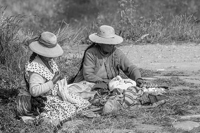 Uros women sitting near the Puerta de Hayu Marca knitting textiles