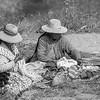 Uros women sitting near the Puerta de Hayu Marca knitting textiles