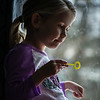 A Girl Blowing Bubbles in the Morning Light