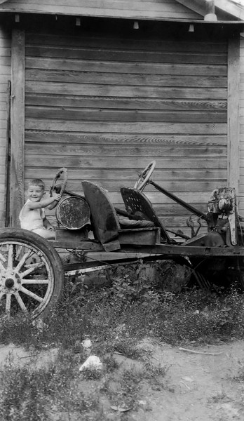 Kid playing on an old car. 1930s probably.