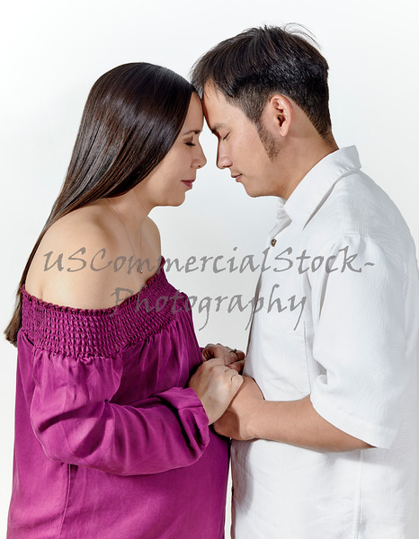 Expecting Young Couple with Foreheads touching and Eyes Closed