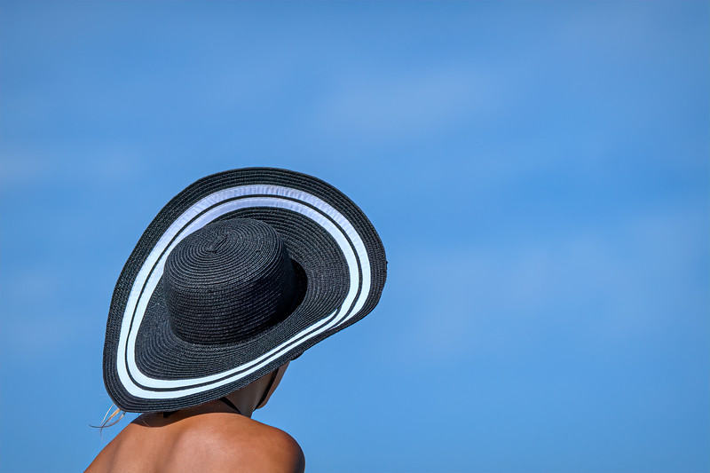 Black sun hat and tanned shoulders on Palm Beach Municipal Beach, Palm Beach, Florida