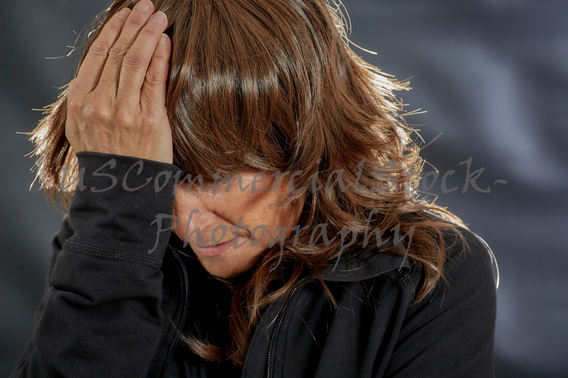 Woman with eyes closed and holding her forehead