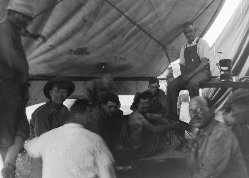 Workers hanging out in a canvas tent, unknown location. Probably 1930s.