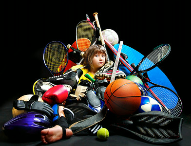 Child under a pile of sports equipment