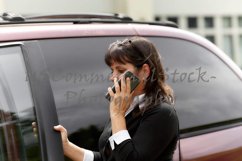 Woman talking on Cell Phone while Entering Car