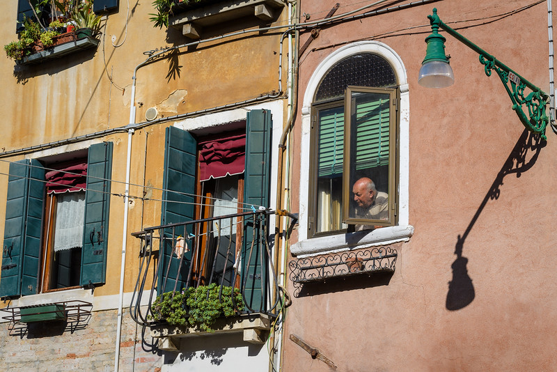 Man looking out window in Venice, Italy