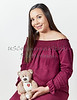 Attractive Pregnant Woman holding a Teddy Bear and Smiling