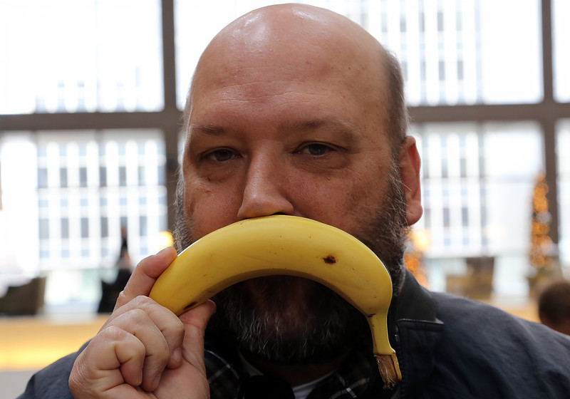 A gentleman wiping his nose with a banana.