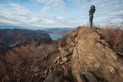 A hiker looks over lake Berryessa from Putah Creek wildlife area in California.