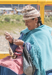 Uros woman sitting on the bridge between Peru and Bolivia, spinning Alpaca wool.
