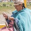 Uros woman sitting on the bridge between Peru and Bolivia, spinning Alpaca wool.