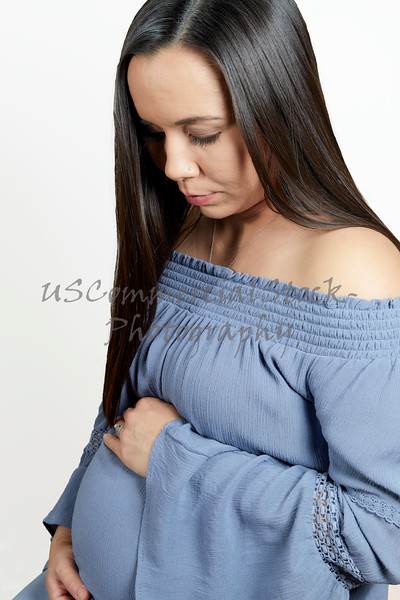Pregnant Woman with Hands on Tummy while looking Down