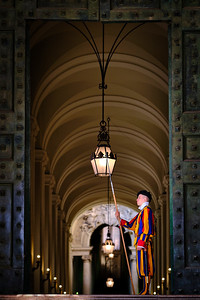 A Swiss guard stands guard at the Bronze Door at the Vatican City, Rome