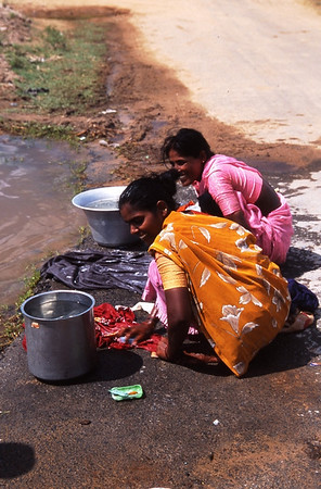 These young women in Kanchipurim are washing clothes by rubbing them on the road and using a bar of hand soap as the washing agent.  The water they are using is not very clean, and the combination of the abrasive washing style and the quality of the water results in clothes that often get tears and holes and are not as clean as if they were washed in cleaner water.  Never the less, in this part of India, there is a severe lack of potable, clean water.