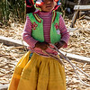 Uros Girl helping tether a reed boat to their floating island.